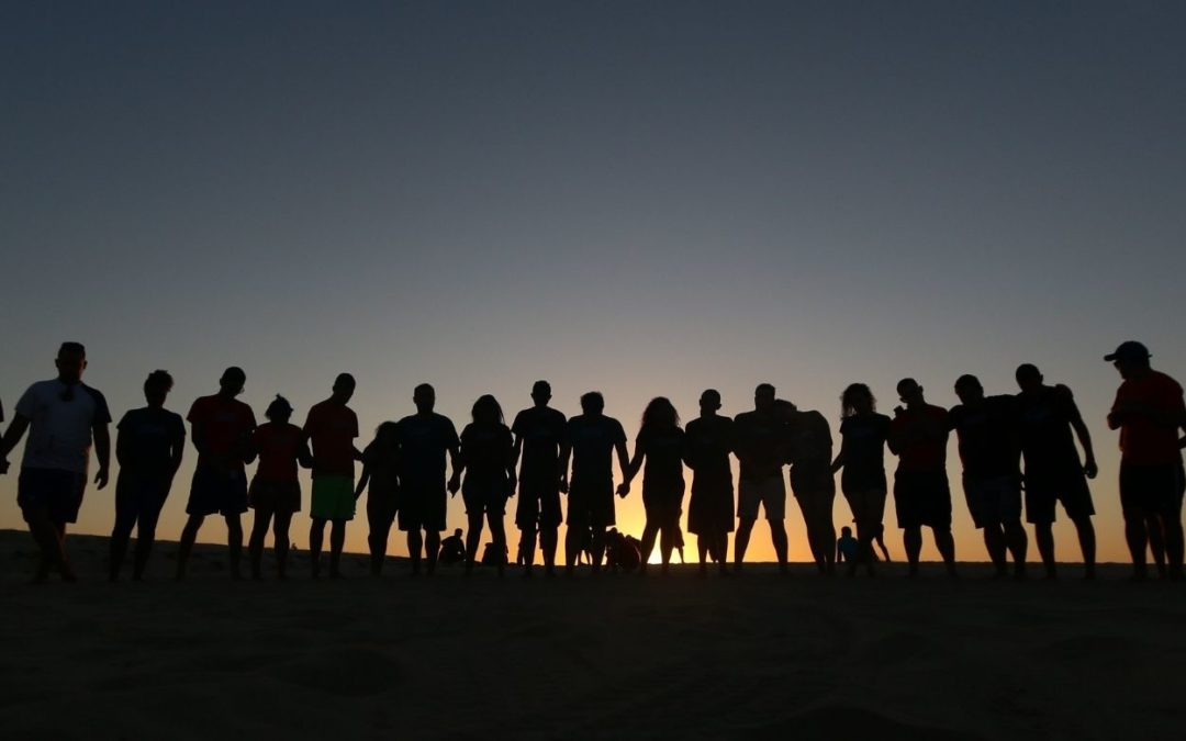 group of people holding hands on the horizon symbolizing the fact that you are never alone