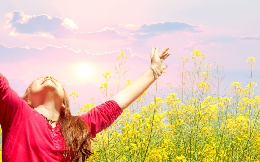 A woman raising her arms to the sun in a flower field representing The Event and You