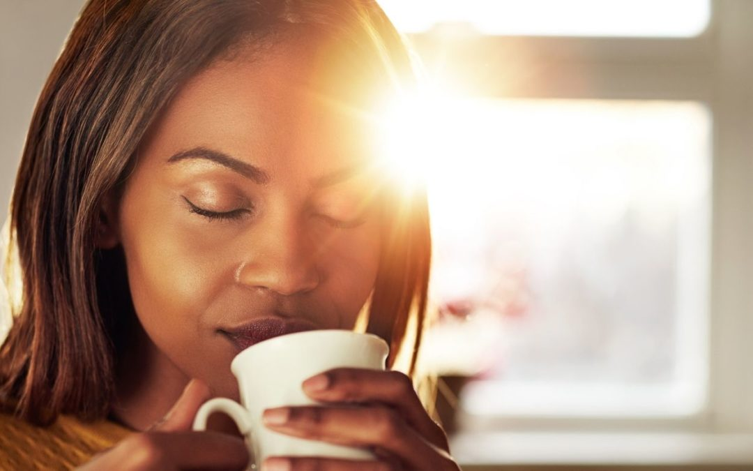 woman drinking coffee while the sun comes up with her eyes closed representing being present